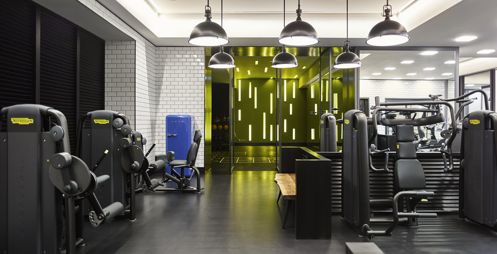 The gym is an industrial space, featuring black paneling and white subway tile.