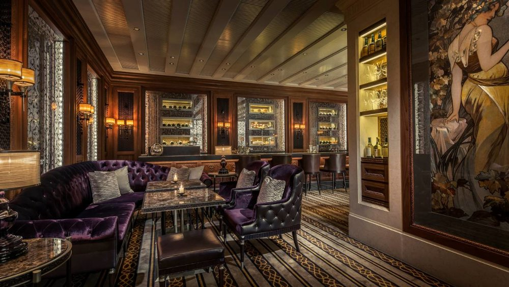 A moody decadence pervades, made rich by dark, stitched leather and timber walls, textured fabrics and ceiling coffers of bronzed glass. At the focal center sits the bar, a theatrical statement in backlit, richly hued art glass.