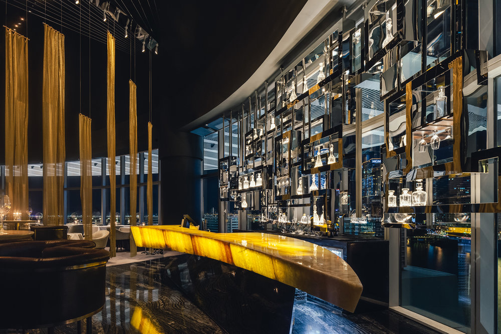 The tables are tall, the floor is dark marble, and the bar itself is designed to be a floating crescent moon of backlit onyx.