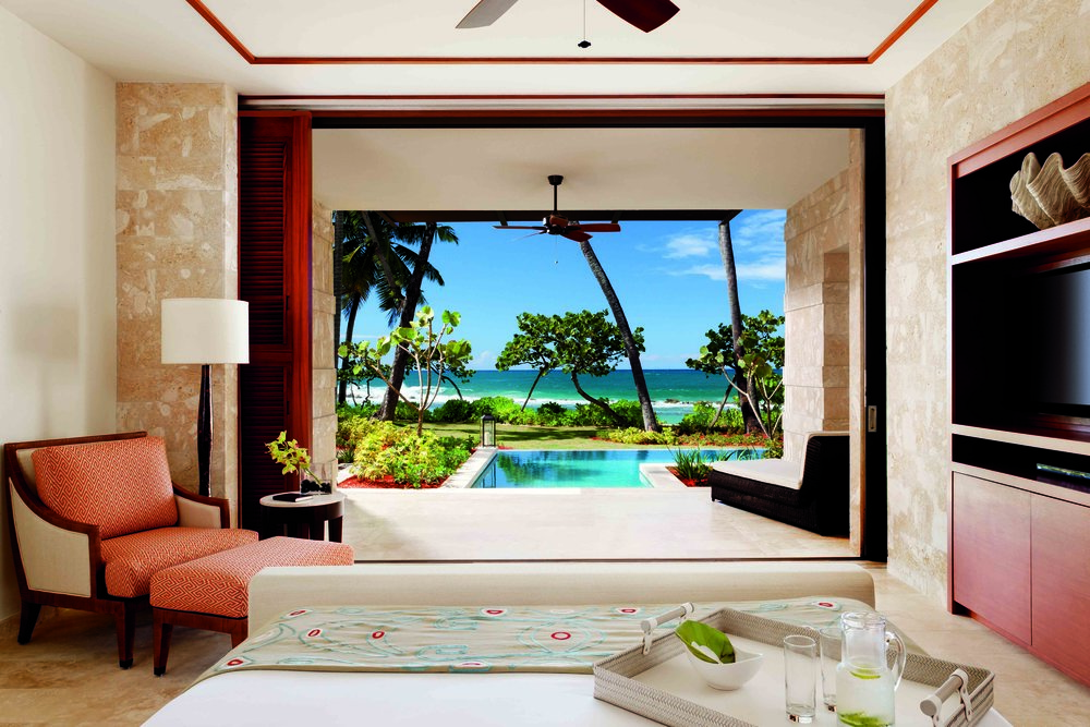 The bed, resting in the center of the room, faces the ocean.