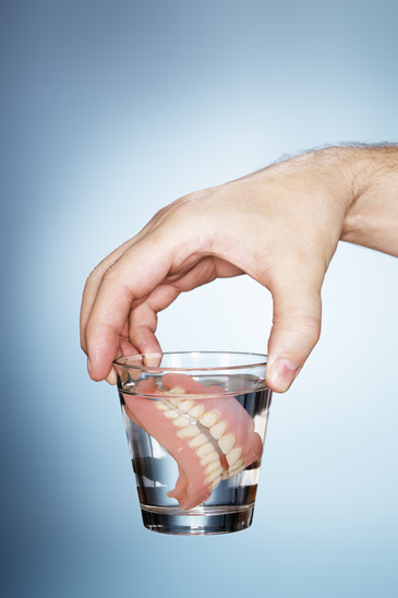 Man holding a glass containing old dentures