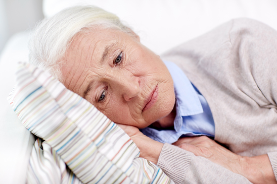 Sad senior woman sleeping on pillow at home