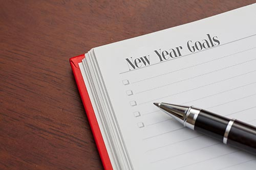conceptualnotebook-on-a-wooden-table-open-diary-and-pen-with-new-year-goals-words