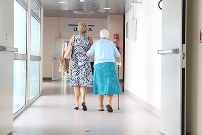 Elderly mother and daughter walking down hall