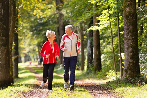 senior-couple-doing-sport-outdoors-jogging-on-a-forest-road-in-the-autumn
