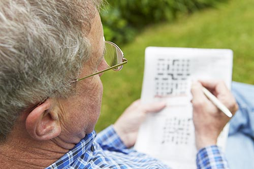 senior-man-doing-crossword-puzzle-in-garden