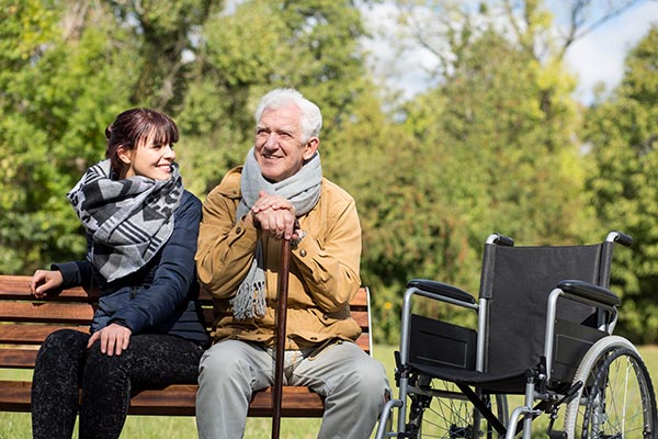Older man and home care assistant on park bench