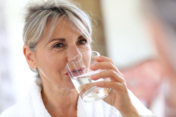 Older adult with water glass
