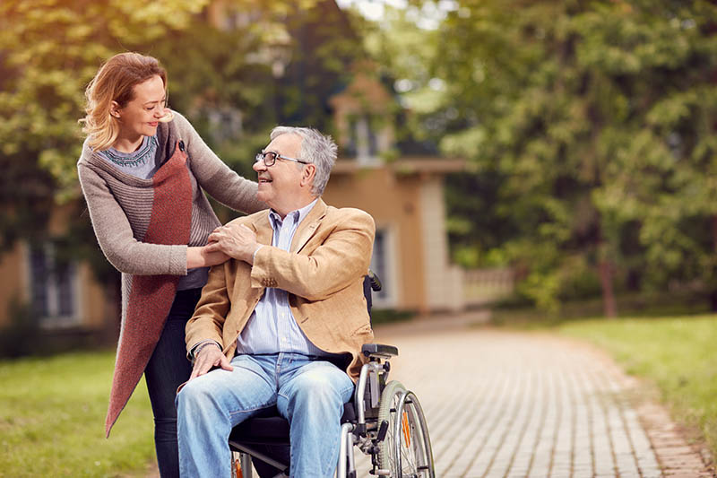 Elderly man in wheelchair with her cheerful daughter enjoying to visit together in sunny day