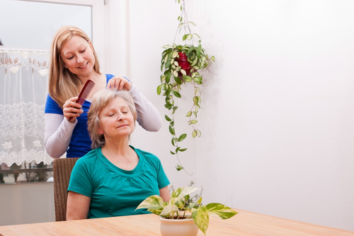 Home health caregiver brushing hair of older woman