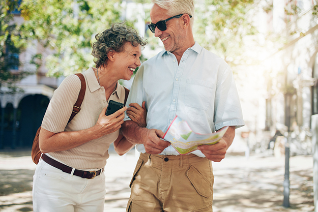 retired couple walking around town with map