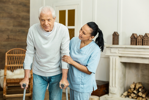 helpful caregiver assisting senior man