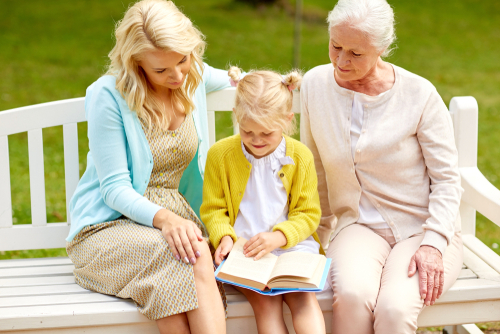 happy smiling woman with daughter and senior mother sitting on park bench