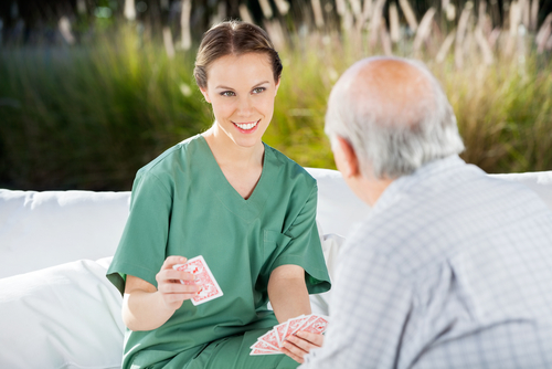 Smiling female nurse playing cards with senior man at nursing home