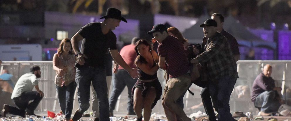 People carrying an injured concert goer to safety.