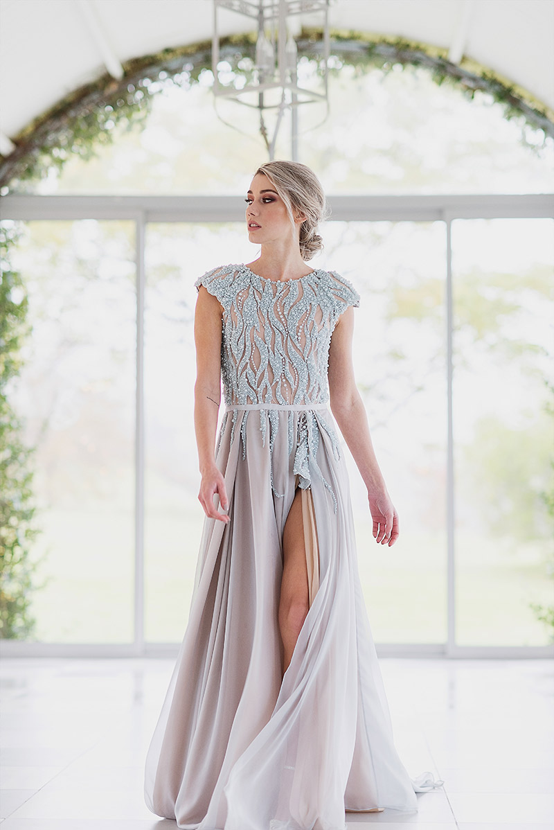 Arielle - Light blue pearl beading on a peach lined bodice with pleated chiffon skirt and thigh high slit.Size 8 - 10SALE PRICE: R15 000