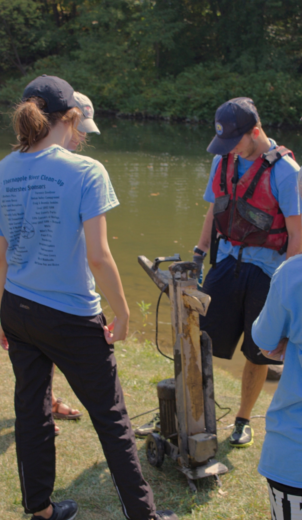 Silverhart(in red) looking at their other big find,an electric log-splitter. It was so heavy that he had to drag it down the riverbank to a place where Duarte, his canoe partner, could maneuver close to load it in underneath the car rooftop they had already recovered.