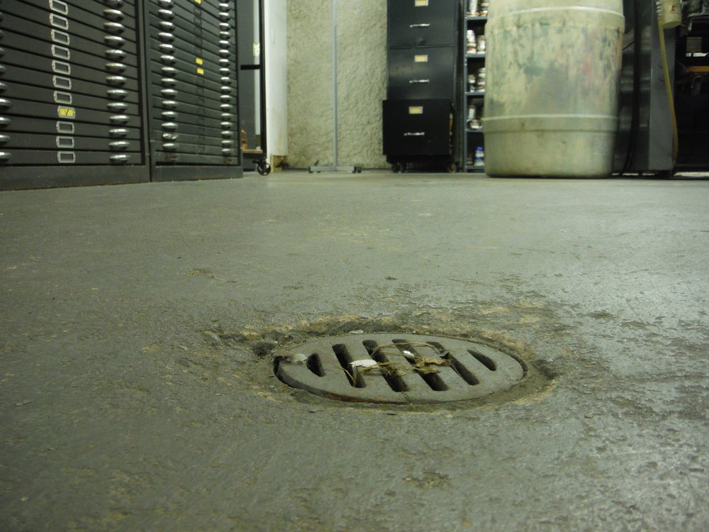 One of the floor drains in Robin Dana's shop. He often uses a squeegee to push water that has seeped through the walls into the drain.