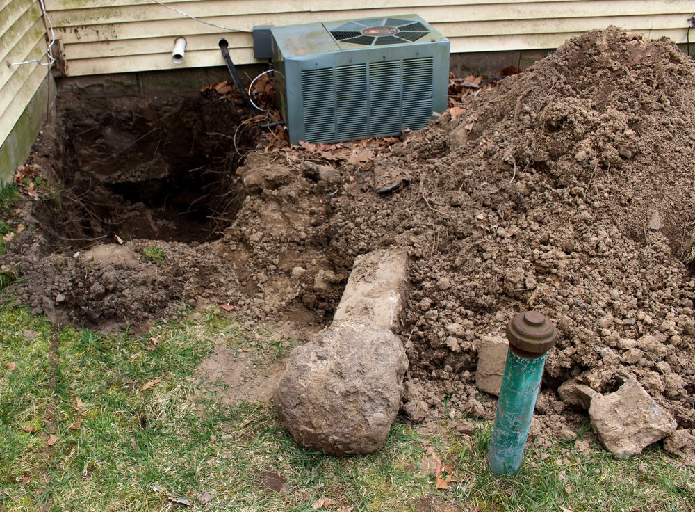 This photo shows the difficulty of proving Resseguie's situation. You can see the well in the foreground. The sewer line is barely visible, on the bottom right of the hole that was dug. The air conditioner sits in the way of any more excavation.