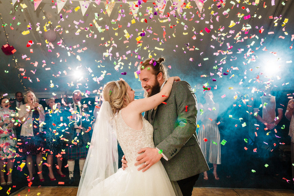 Newlyweds during their first dance as a colourful confetti canon explodes above them
