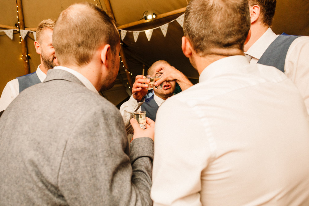 A groom doing shots with his friends