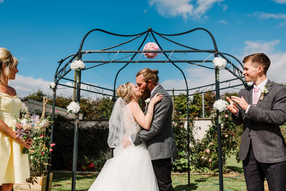 A bride and groom having their first kiss at a Leeds garden wedding