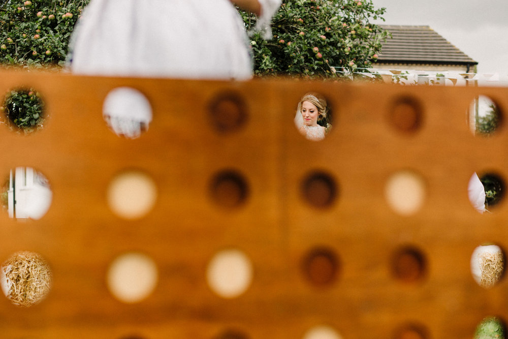 A shot of a bride through a giant connect 4 lawn game