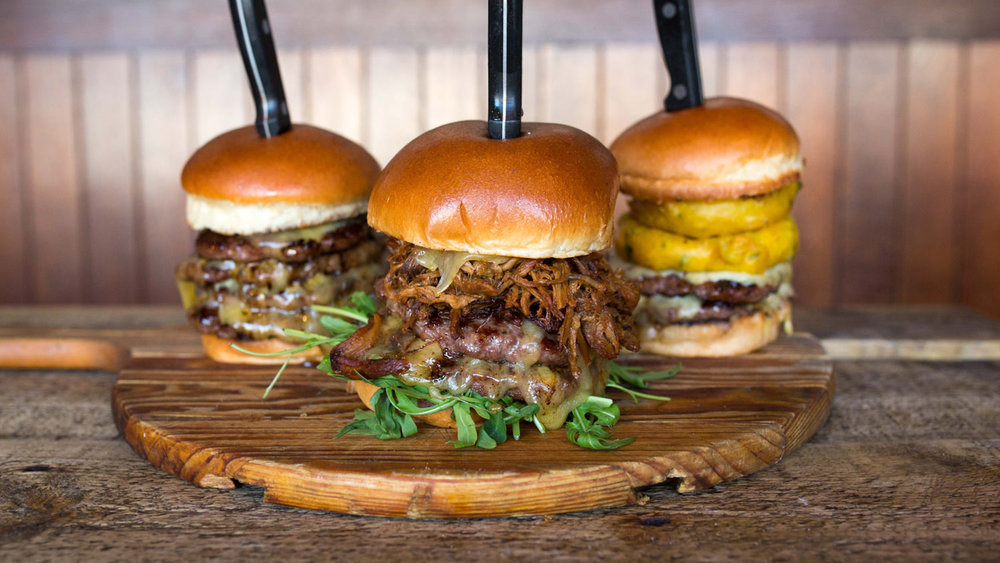 Three large burgers on a table