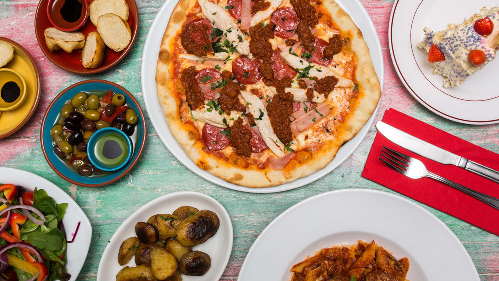 An aerial shot of a pizza and other Italian food on a table