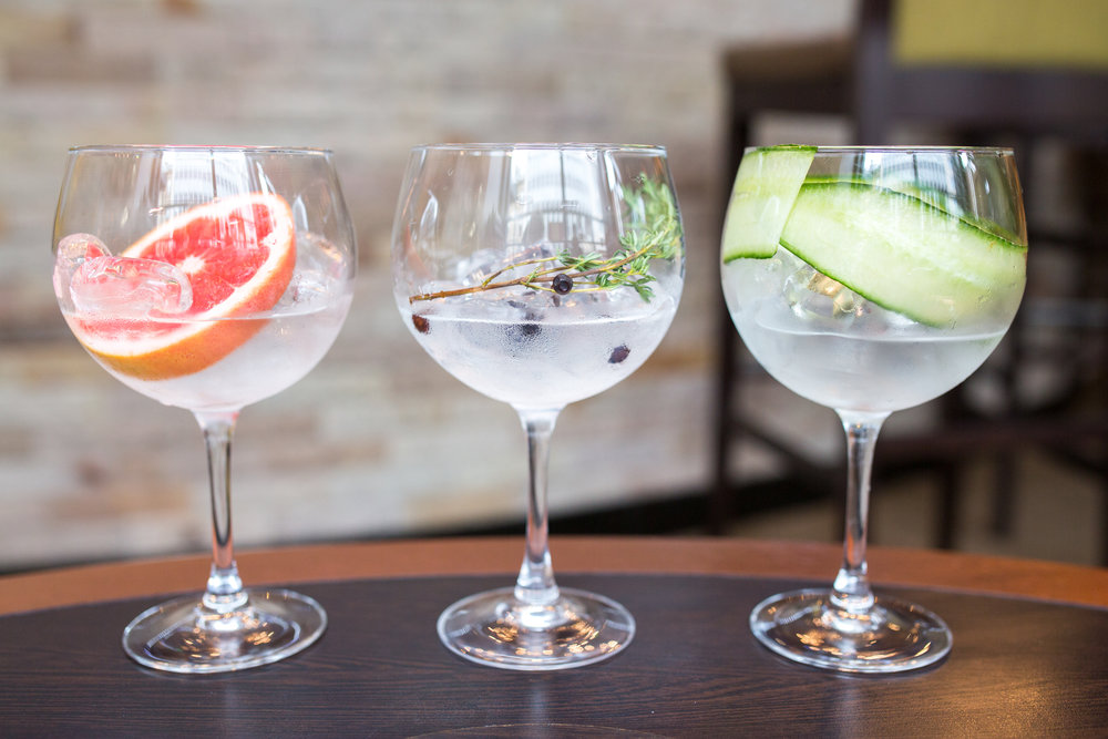 Three cocktails lined up on a table