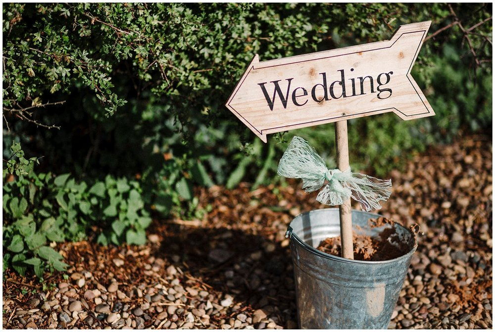 A wooden sign in a bucket pointing to a wedding