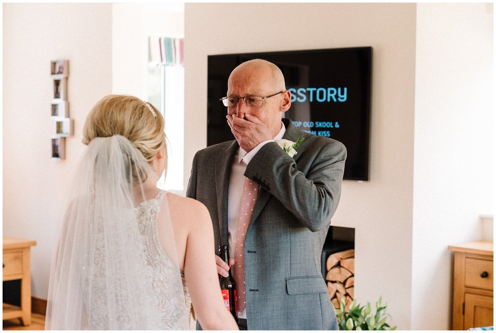 father of the bride crying as he sees his daughter in her wedding dress.jpg