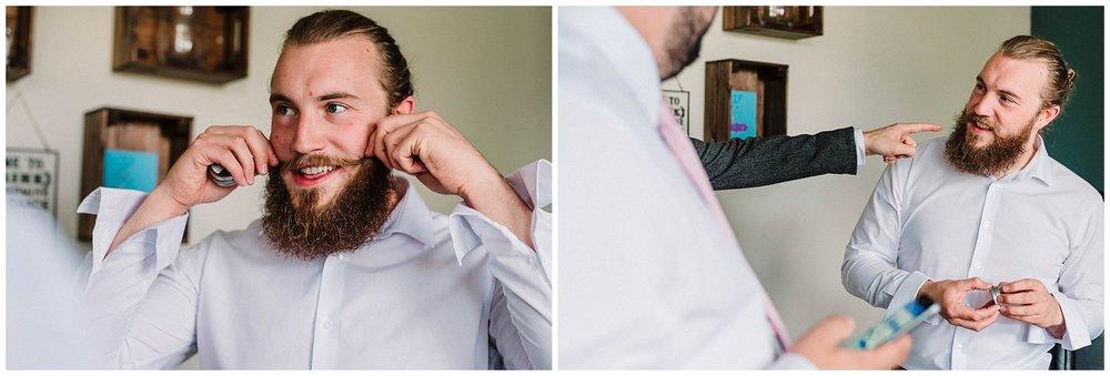 a groom tweaks his moustache before his wedding.jpg