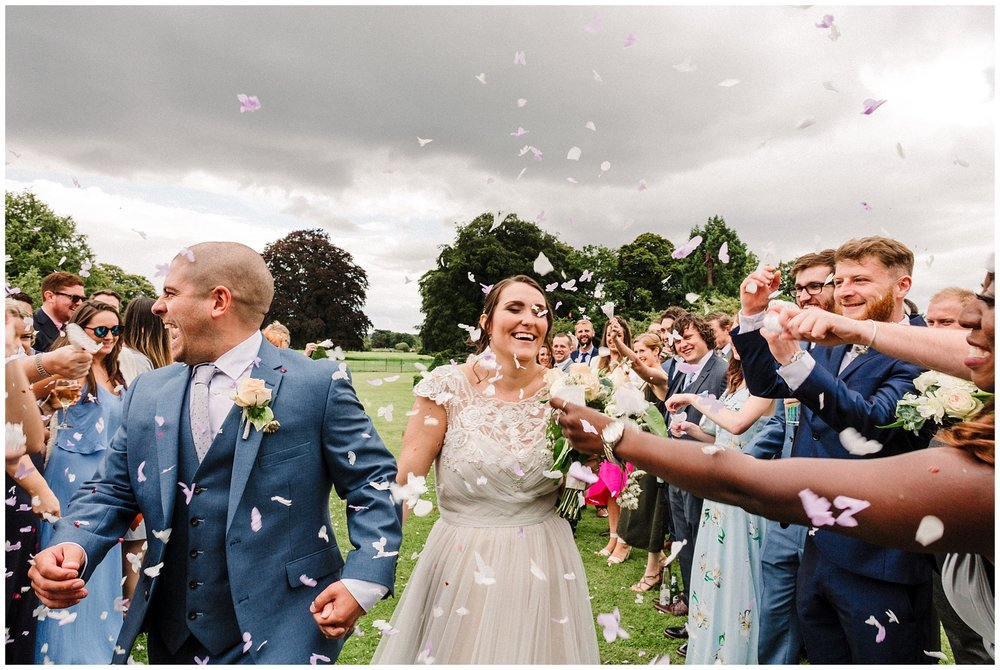 guests throw confetti on a bride and groom as they walk down the aisle