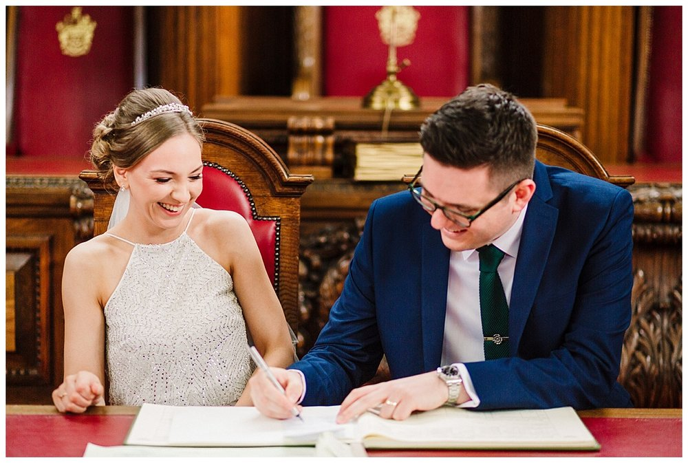 bride and groom sign the register in the council chamber room at islington town hall