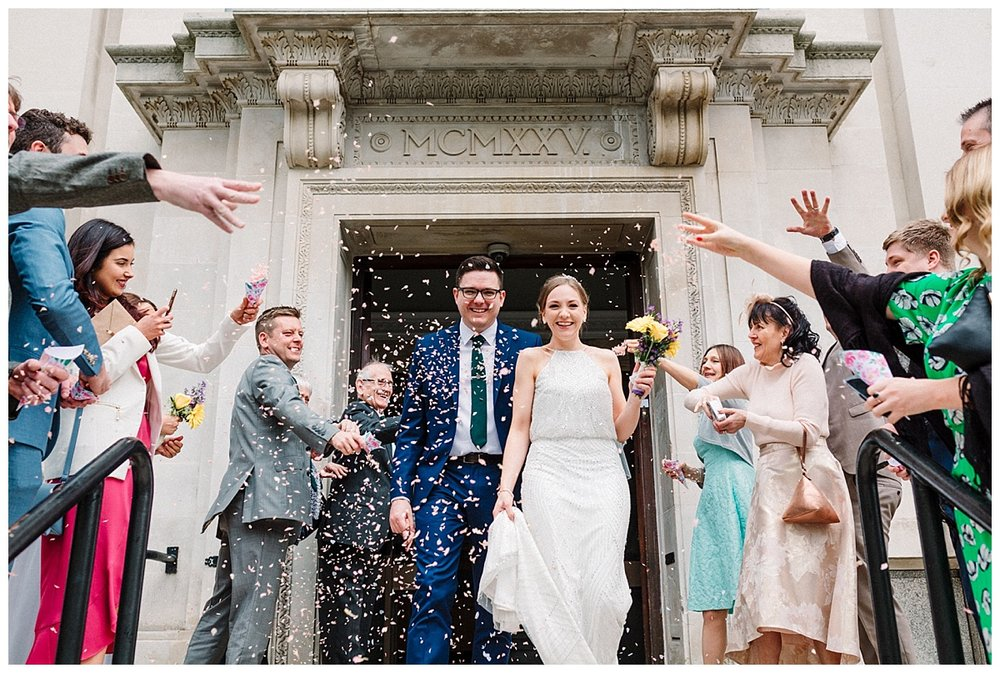 bride and groom walking through confetti as they leave islington town hall