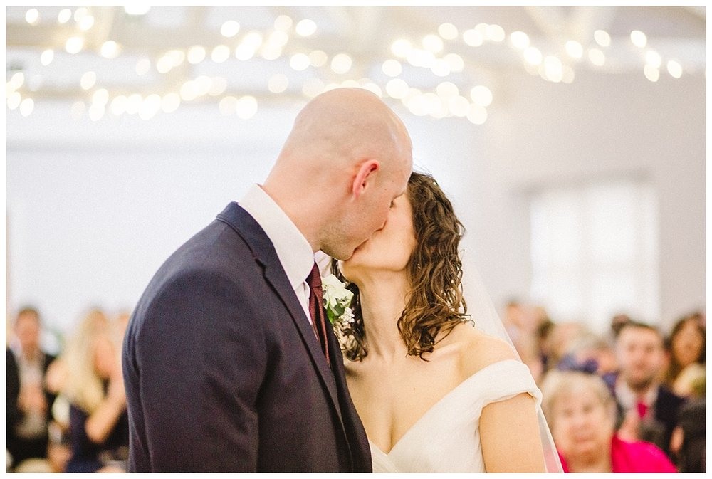 a bride and groom have their first kiss at a barn wedding in hertfordshire
