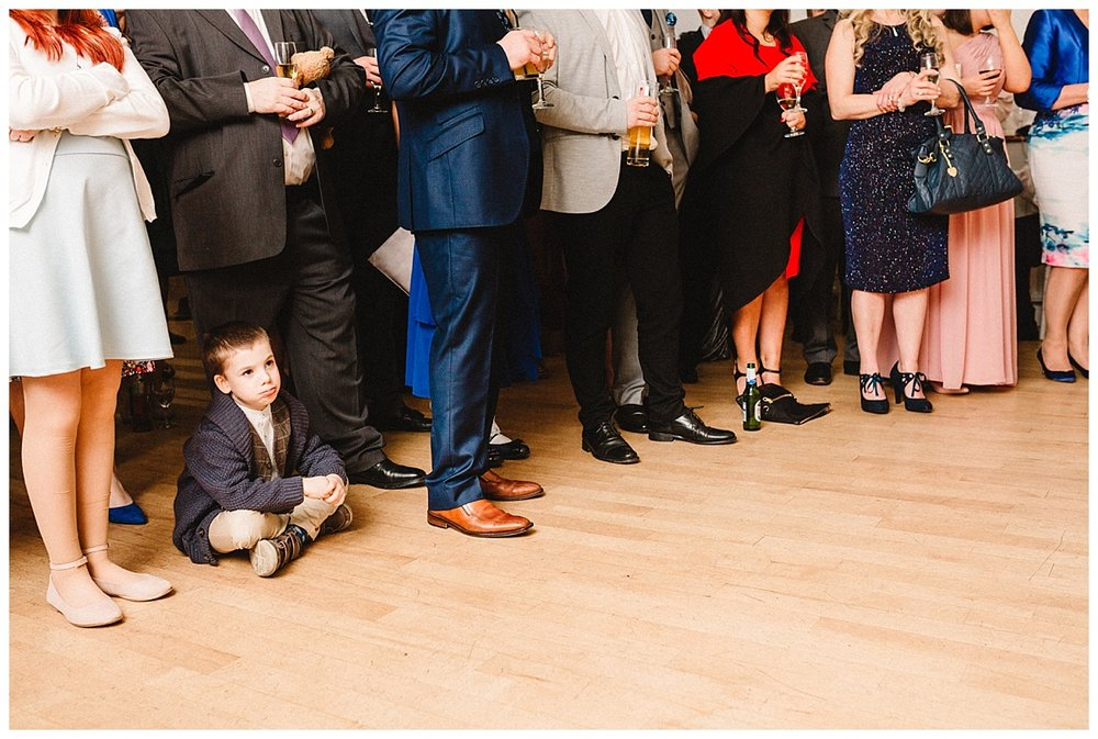 a young boy is bored during wedding speeches