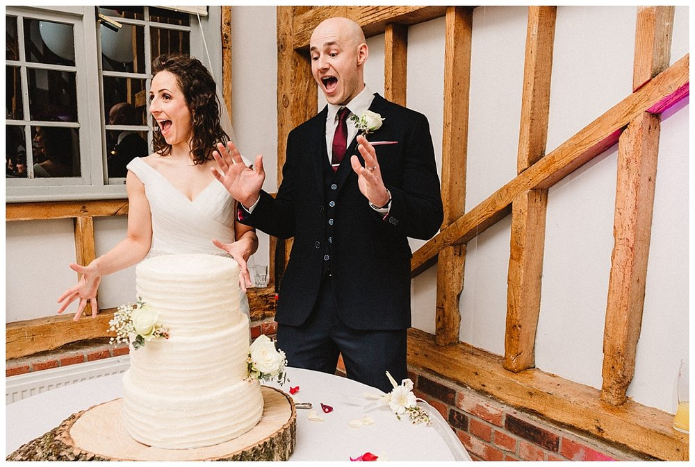a bride and groom pulling silly faces next to their wedding cake