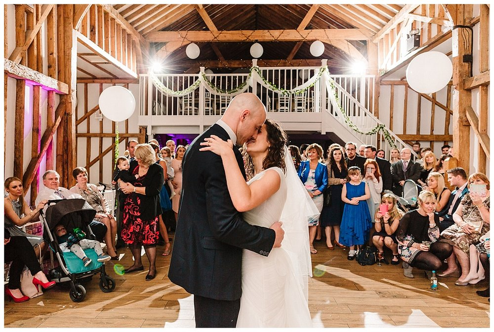 a bride and groom doing their first dance in a barn