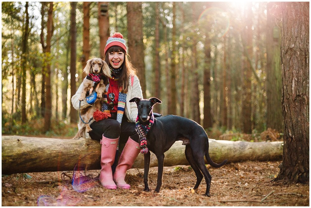 A woman sitting on a log in the woods and smiling with her two dogs