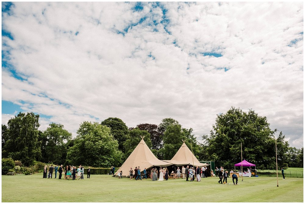 Wedding guests outside a tipi in the gardens of Scampston hall in Yorkshire