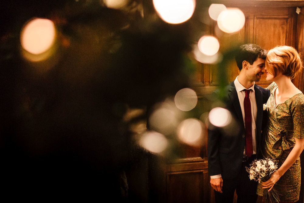 An informal bride and groom standing beside fairy lights at night