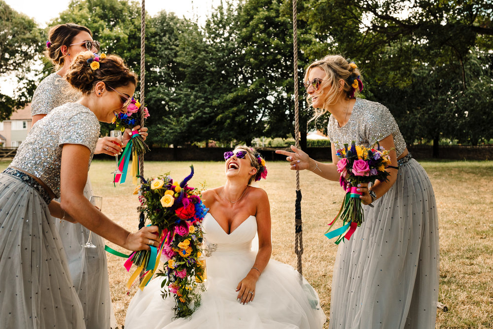 A bride and her bridesmaids sat on a swing laughing