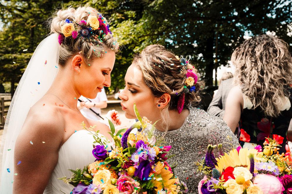 A bridesmaid blowing confetti off a bride's chest