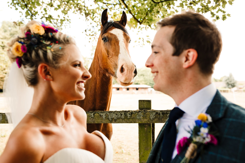 A horse looking at the camera between a laughing bride and groom