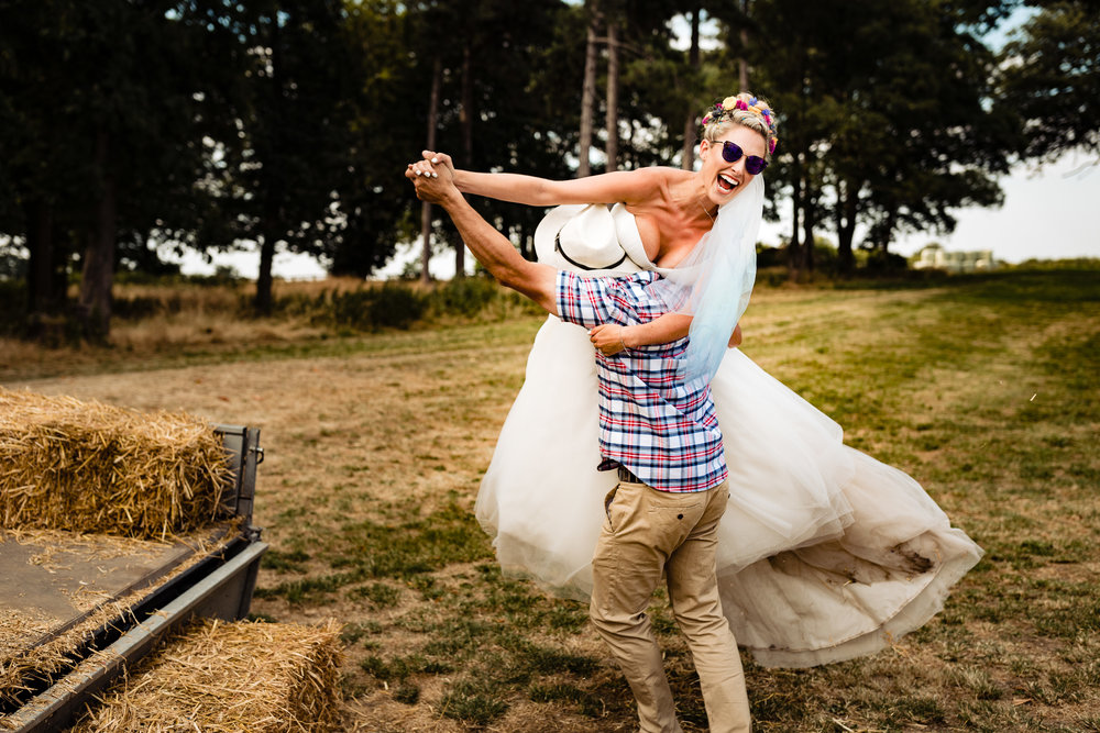 A bride being lifted off a tractor at a farm wedding