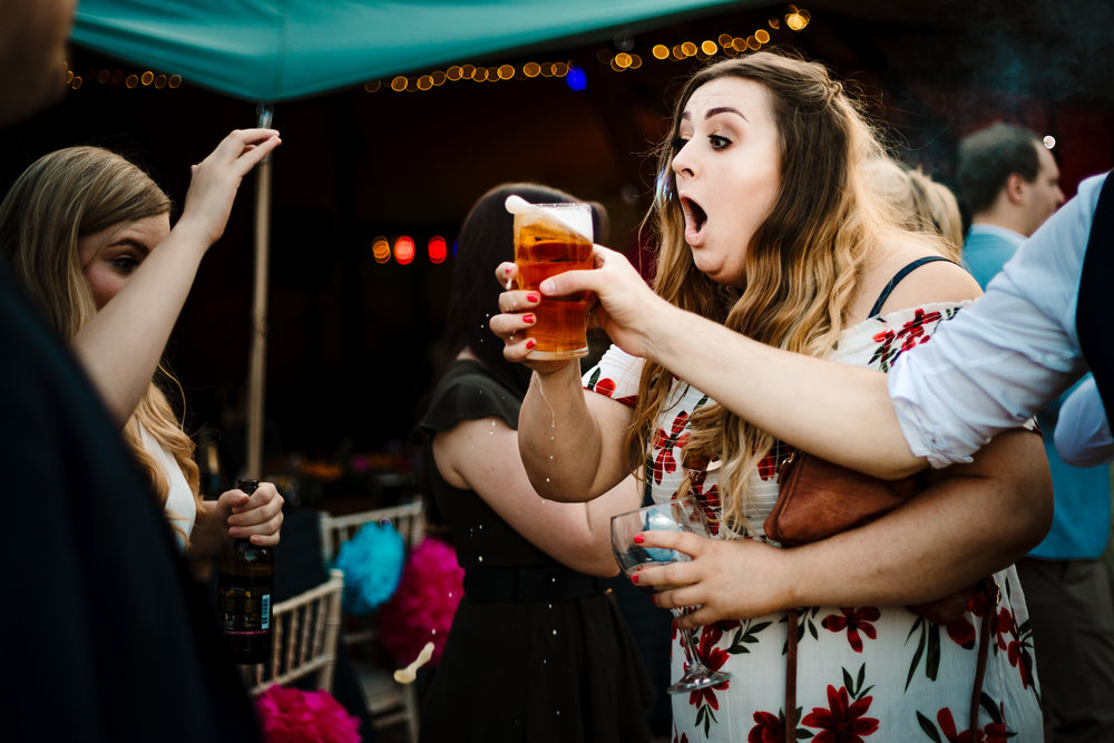 A wedding guest pulling a shocked face as she almost spills her drink