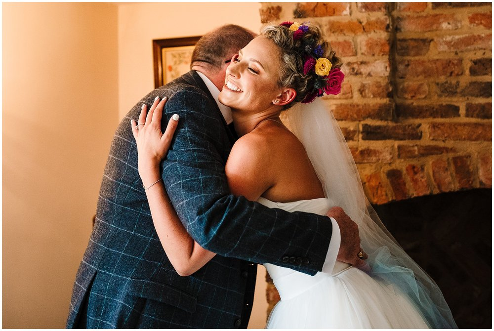 A bride hugging her dad on the morning of her wedding