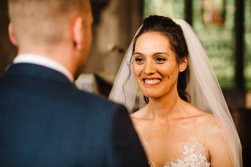 A bride looking adoringly at her groom at the top of the aisle